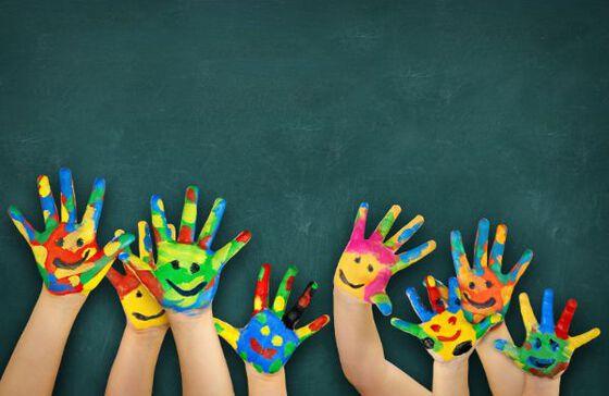 Barn som vinker med ansikter malt på hendene sine