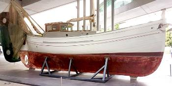 Wooden boat, maybe 20 meters long. A small cabin. White and brown colours. Photo.