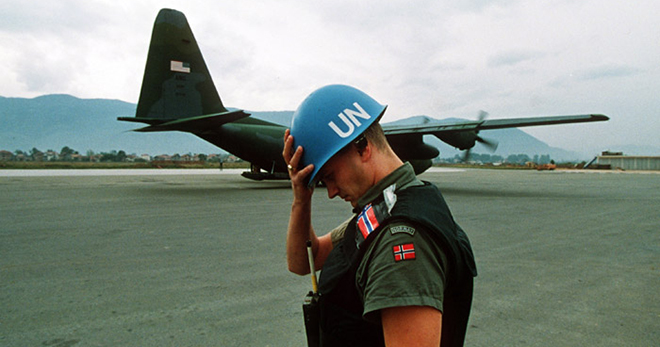A United Nations peacekeeper from Norway holds his helmet as a Hercules C-130 transport plane lands at Sarajevo airport in the summer of 1992