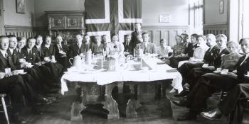 Black and white photo. Men and women are gathered around a big table. The Norwegian flag is hanging on the back wall.