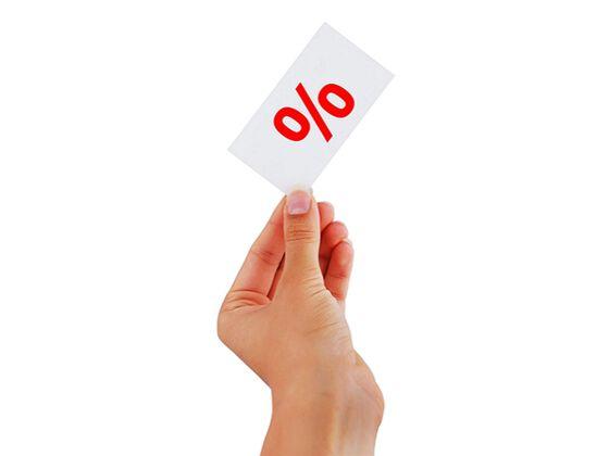 Hånd som holder opp en hvit lapp med rød prosenttegn på