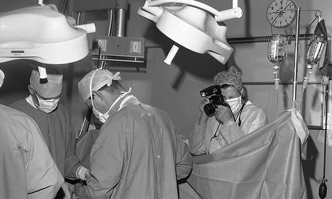 Old photo of photographer in operating theater.