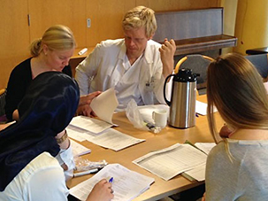 Fire personer i diskusjon rundt et bord med papirer