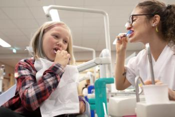 Bildet viser en ung jente, Anna, på 8 år som lærer å pusse tenner av en tannlegestudent.