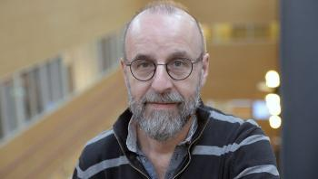 Middelaldrende mann med skjegg, lite hår på hodet, briller i stripete skjorte.