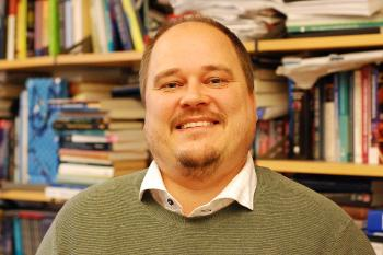 Bilde av professor Carl Henrik Knutsen foran bokhyllenpå kontoret på Blindern