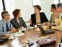 Fem personer diskuterer rundt et møtebord