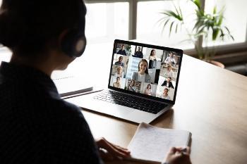 Kvinne med headset som sitter foran en laptop der det foregår et digitalt møte