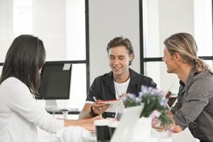 En kvinne og to menn i en livlig samtale