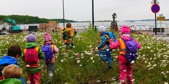 Barn i blomstereng på jakt ette.