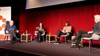 Fire personen sitter på en scene og snakker sammen. Rød bakgrunn.