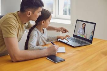 Mann og jente følger digital undervisning på laptop.