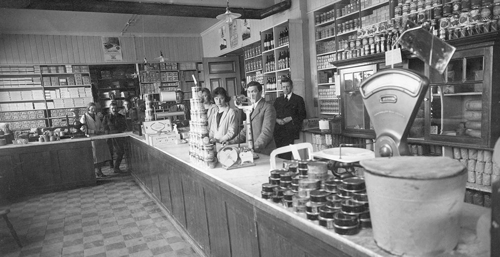 An old black and white-photo of women and men behind the counter at an old fashioned shop.