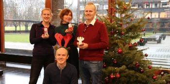 Fire personer som poserer foran juletre