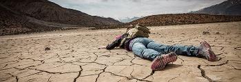 Person ligger på tørket jord.