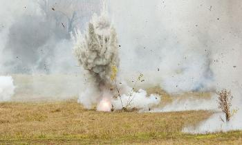 Exploding bomb on grass field