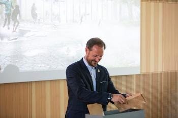 Kronprins Haakon med en frøpose som skal sås i en kasse.