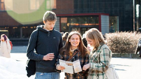 Tre elever i videregående skole som leser en brosjyre ute på campus