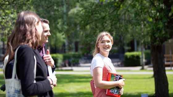 Kollokviegruppe med studenter forflytter seg på campus en sommerdag i juni
