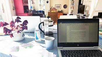 Spisebord med duk med en halvfull kaffepress, en kaffekopp, PC og notater med understrekinger