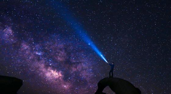 En person ser på stjernene med en lommelykt