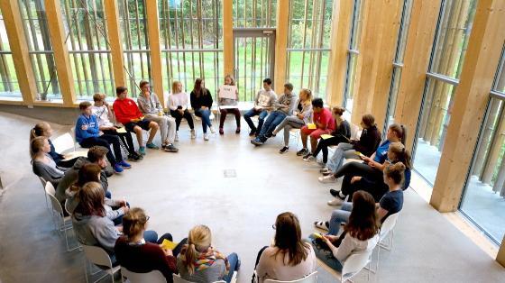 Elever sitter i ring i Henghuset på Utøya som del av et undervisningsopplegg. Foto.