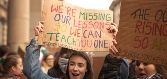 Skoleelev holder plakat der det står we`re missing our lessons so we can teach you one. Illustrasjonsfoto.