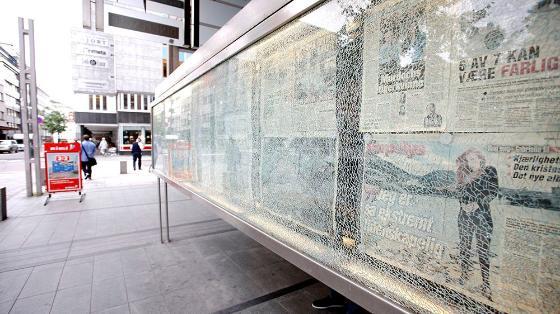 Knust glassmonter med avis-sider bak.