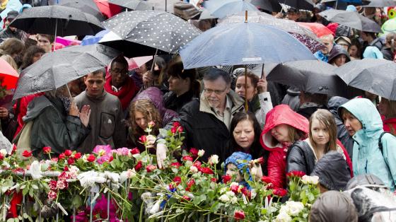 Bilde fra rosetog etter 22. juli for ti år siden. Paraplyer, regn, folk, roser.