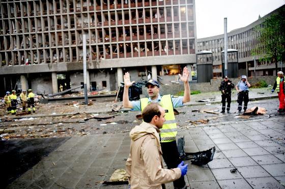 Regjeringskvartalet 22. juli for ti år siden etter at bomben gikk av. Politi og redningsmannskaper på stedet.