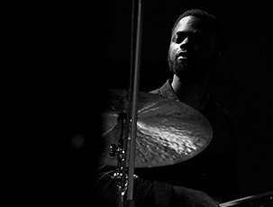 A drummer sits behind a cymbal. Black and white. Photo.