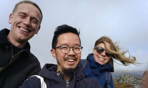 Three people smiling on a mountain