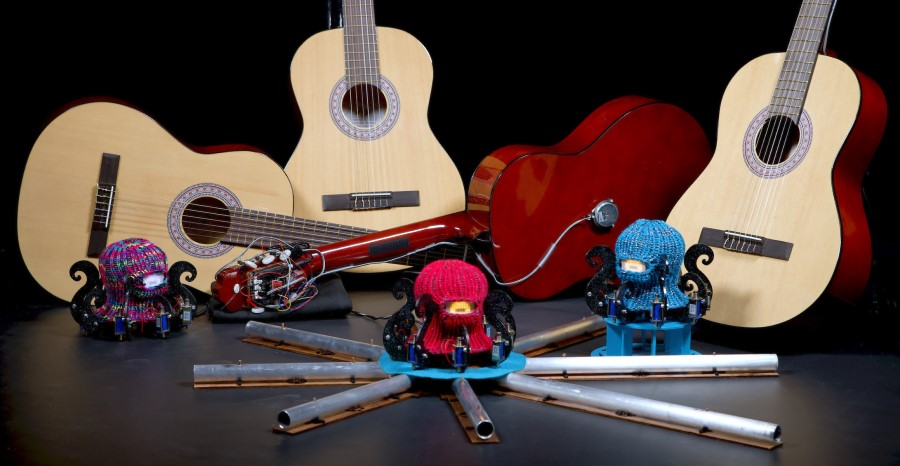 Three Dr. Squiggles-robots with guitars in the background. The robots look like octopuses with knitted balaclavas.