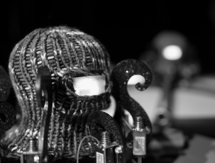 A small, octopus-like robot. Black and white. Photo.