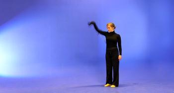 Dame i svart med armen rett ut i et blått rom. Foto.