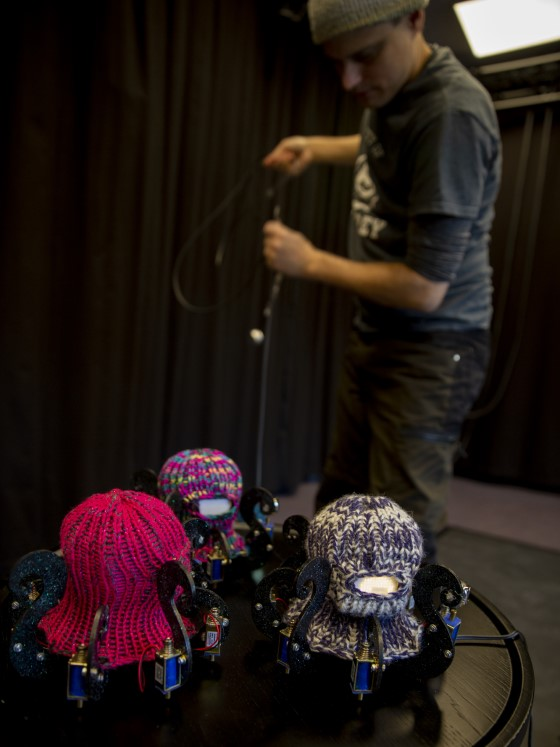 Man standing behind a table with three Dr. Squiggles-robots. The robots look like octopuses with knitted balaclavas.