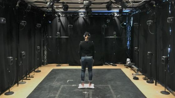 Woman standing in the motion capture lab. She is facing away from the camera.