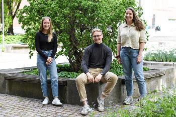 Tre biologistudenter sittende og stående foran et grønt tre.