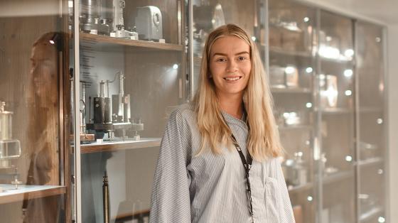smilende kvinnelig student foran ekseperiment-utstyr