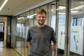 Smilende student Halvard i grå genser i freshe kontorlokaler på Blindern