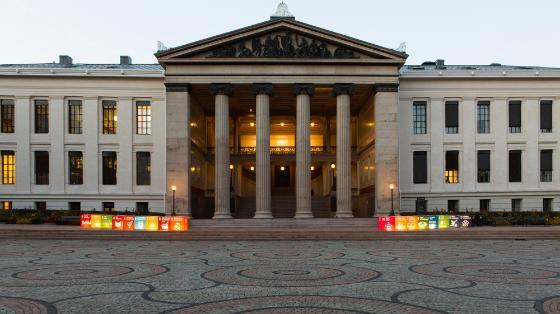UiOs hovedbygning med lysende klosser som symboliserer fns bærekraftmål