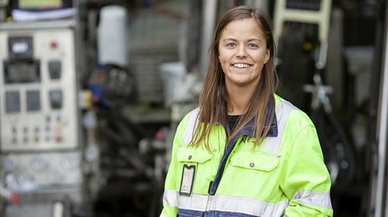 geolog i godt synlige arbeidsklær foran maskineri