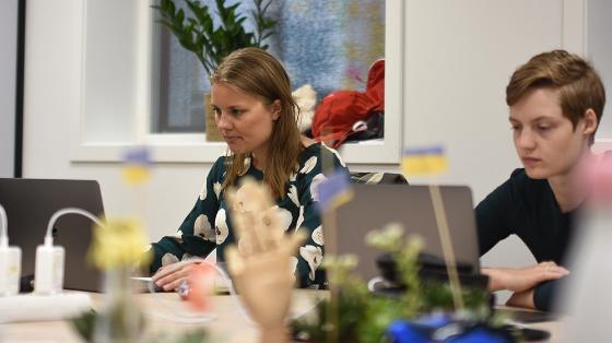 To kvinnelige studenter sitter og jobber i et lyst kontorlandskap med blomster og ledninger