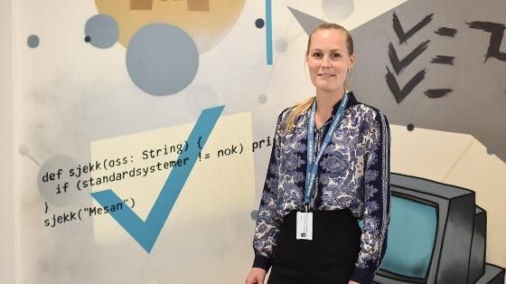 Bilde av Kristine foran en vegg med fin grafikk av koding og kreativitet.