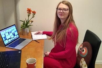 Solveig sitter ved sitt skrivebord på hjemmekontoret, med kaffeekopp, to skjermer og en blomst
