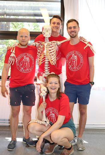 4 smilende studenter iført røde t-skjorter med UiO-logo poserer med et skjelett.