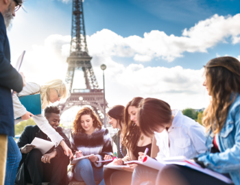 Glade studenter i kollokviegruppe foran Eifeltårnet i Paris.